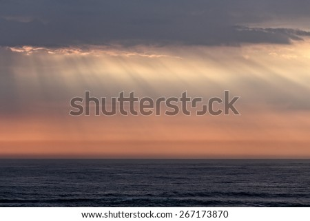 Beautiful orange sea sky just before sunset with sunbeams - stock photo
