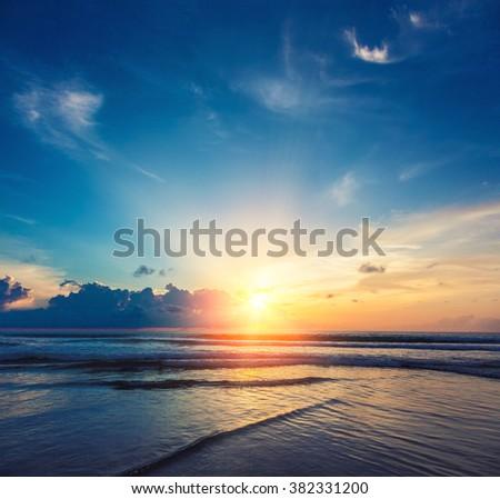 Beautiful orange sun rise with sea and clouds - stock photo