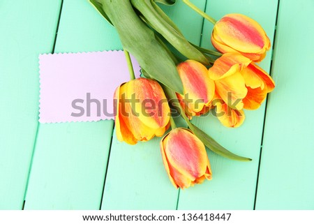 Beautiful orange tulips on color wooden background