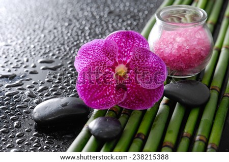 Beautiful orchid with stones and bamboo grove, salt in glass on wet background - stock photo