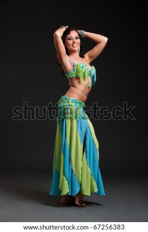 beautiful oriental dancer posing over black background