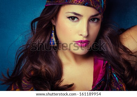 beautiful oriental look young woman with scarf on blue background - stock photo