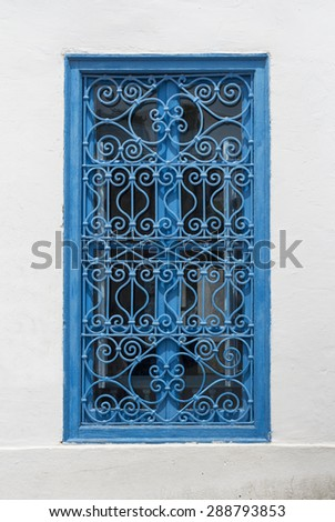 Beautiful ornamental blue windows on a white wall so typical for Tunisia,