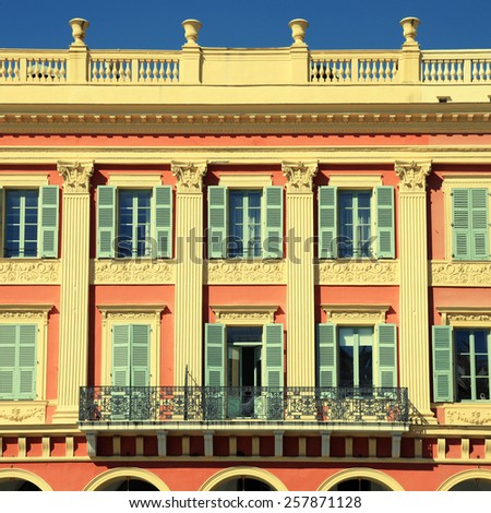 Beautiful ornate red building facade with traditional shutter windows in the city of Nice,Cote d'Azur,  France. Square toned image - stock photo