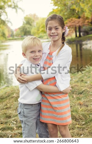 Beautiful outdoor portrait of a cute boy and girl with a scenic fall background
