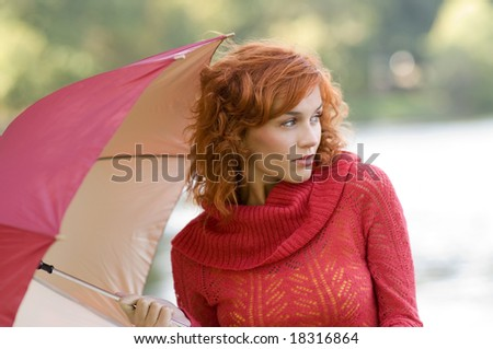 beautiful outdoor shot of woman in red with umbrella on green background