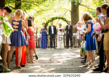 Beautiful outdoor wedding ceremony at park with lot of guests - stock photo