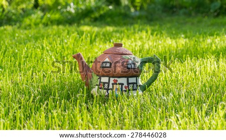 Beautiful painted ceramic tea in a traditional style on the background of green grass - stock photo