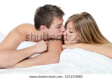 Beautiful pair lays in bed on white - stock photo