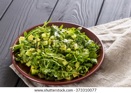 Beautiful Paleo Green Salad with Cucumber and Avocado on a Dark Grey Wooden Background, Horizontal