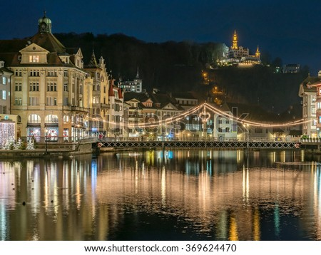 Beautiful Panorama Night view over old town city center skyline cityscape, Harbor, Christmas Light Decorated Krongasse Bridge and famous white Castle Gutsch on a hill from Lake Lucerne, Switzerland