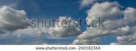 Beautiful panorama of fluffy white clouds in blue sky showing forces of nature. - stock photo