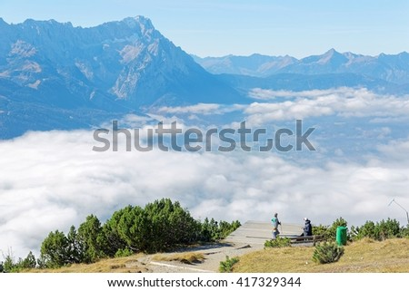 Beautiful panorama of Mountain Zugspitze above clouds from top of Mount Wank in Garmisch Partenkirchen, Bavaria Germany, with view of a paragliding platform at cliff edge & villages down below clouds - stock photo