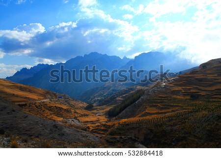 beautiful panorama of mountains and agriculture with sun shines through a cloudy sky in the sacred valley in peru