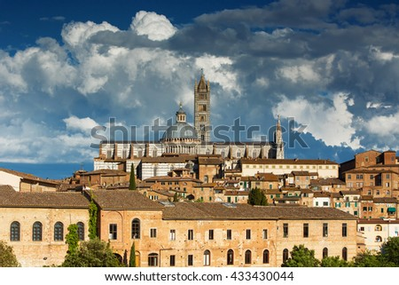 Beautiful panoramic view of the historic city of Siena at sunset with an amazing cloudscape on an idyllic summer evening, Tuscany, Italy - stock photo