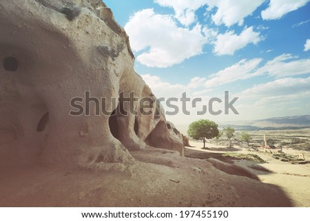 Beautiful panoramic view to the cave from the Uchisar town's castle in Turkey with the tree in the centre, Cappadocia region - stock photo