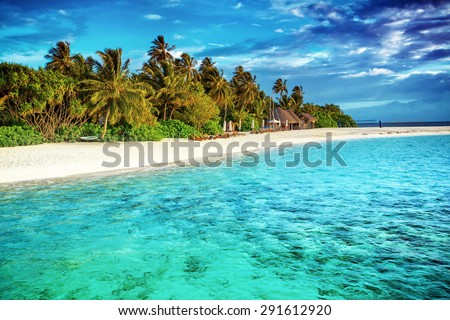Beautiful paradise beach, luxury tropical resort, turquoise transparent sea around the island with fresh green palm trees on the coast, summer vacation on Maldives, Asia - stock photo