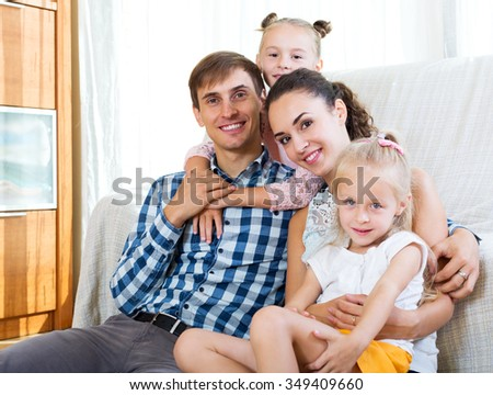 Beautiful parents with two daughters relaxing at home