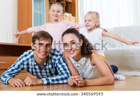 Beautiful parents with two little daughters relaxing at home. Focus on the parents