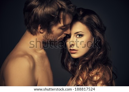 Beautiful passionate naked couple in love. Over black background.