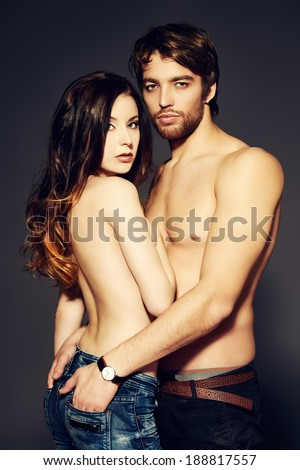 Beautiful passionate naked couple in love. Studio shot.