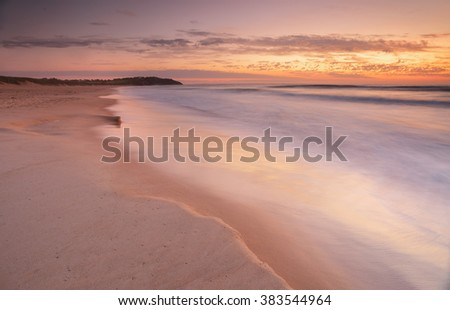 Beautiful pastel shades in the sands and water wash over this 4 second exposure at dawn sunrise, near Dee Why Lagoon and Long Reef Beach, Collaroy - stock photo