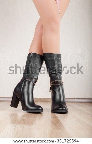 Beautiful patent leather boots with slender legs - stock photo