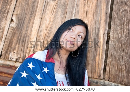 Beautiful patriotic Asian woman wrapped in an American flag thinking about her freedom. - stock photo