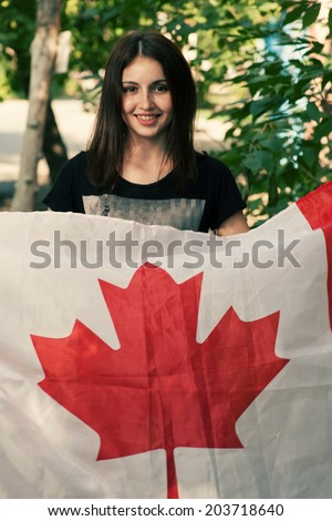 Beautiful patriotic vivacious young woman with the Canada flag held in her outstretched hands standing in the summer sunshine. Canada day - stock photo