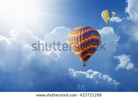 Beautiful peaceful background - hot air balloons flies in blue sky with white clouds - stock photo