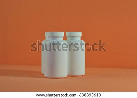 Beautiful peach background. Closed Bottle for pills.