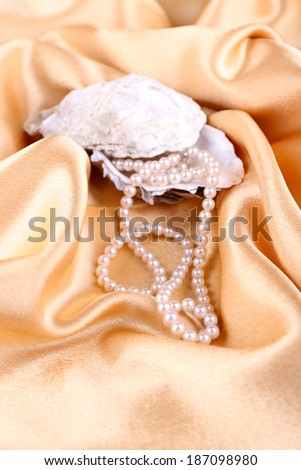 Beautiful pearls in shell on golden silk cloth - stock photo