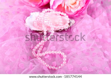 Beautiful pearls in shell on pink cloth - stock photo