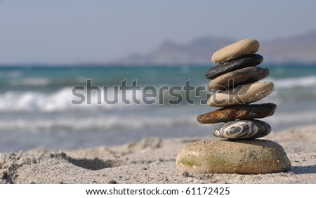 beautiful pebble stack on a sandy beach (sea on the background) - stock photo