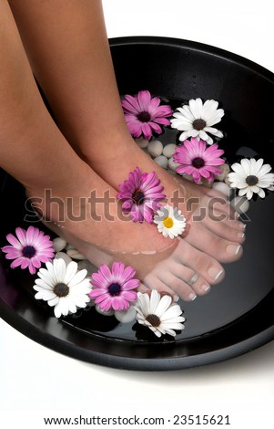 Beautiful pedicured feet and manicured hand with colorful spring daisies in a spa - stock photo
