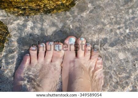 Beautiful pedicured feet under crystal water on te beach - stock photo