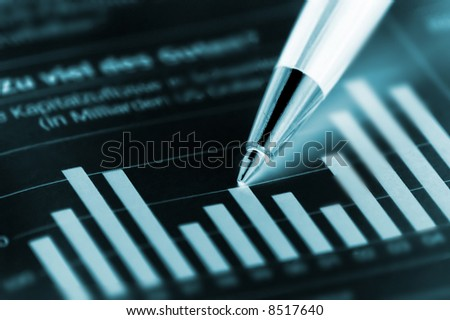 Beautiful Pen pointing on a diagram on an finance newspaper - stock photo