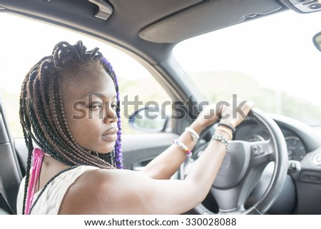 Beautiful pensive african female driver sitting in the car.
