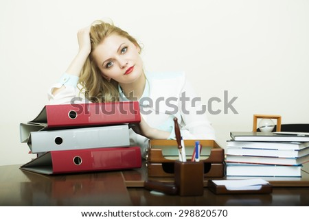Beautiful pensive blonde business woman sitting in office at table with many documents books files folders has a lot of work on white background copyspace, horizontal picture - stock photo