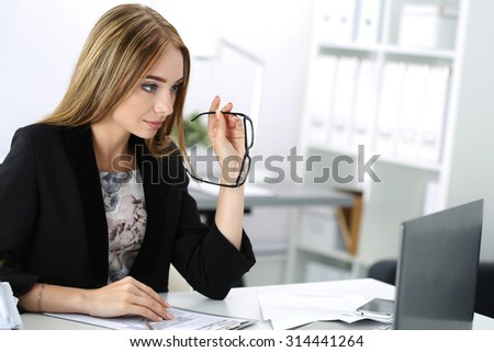 Beautiful pensive businesswoman sitting at her working place at the office and holding glasses in her hand. - stock photo