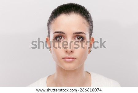 Beautiful pensive woman looking at camera with sad expression