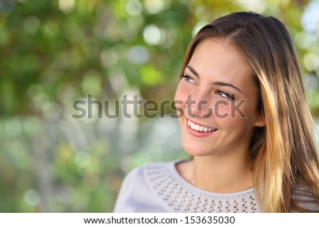 Beautiful pensive woman smiling looking above outdoor with a green unfocused background