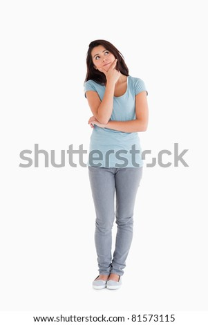 Beautiful pensive woman standing against a white background - stock photo
