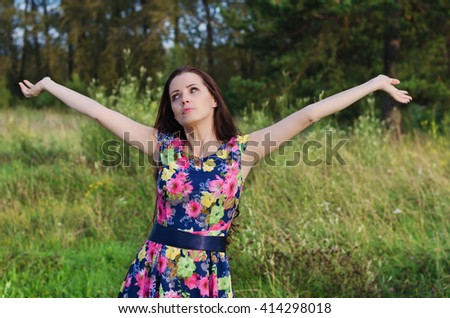 Beautiful pensive woman with long hair standing in a forest glade on a summer evening with their hands up - stock photo