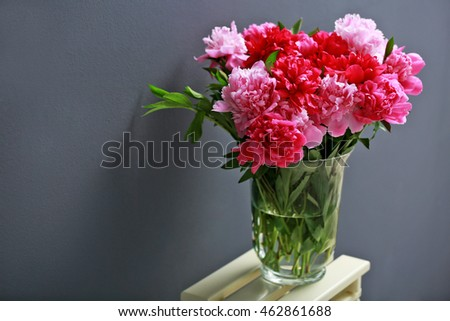 Beautiful peony bouquet on dark wall background