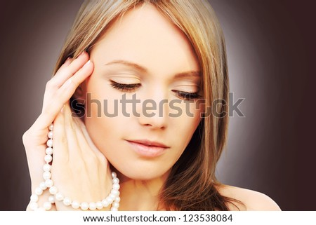 Beautiful perfect girl with pearls jewelry - stock photo