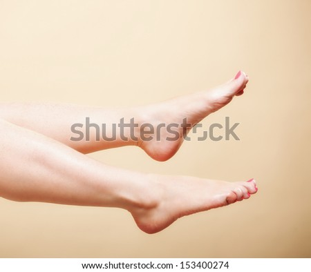 Beautiful perfect long naked woman girl legs barefoot body care pedicure on orange - stock photo