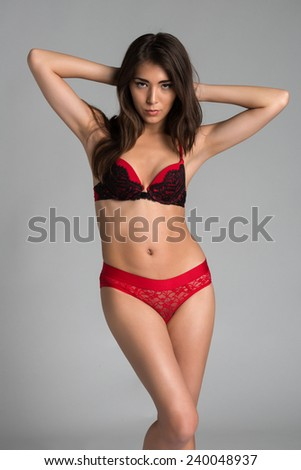 Beautiful petite Eurasian woman in red and black lingerie