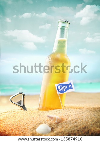 Beautiful photo of a chilled beer and a bottle opener on the beach tagged as Kapt'n. - stock photo