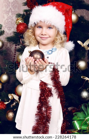 beautiful photo of cute little girl 5 years old with blond curly hair decorating Christmas tree at home - stock photo